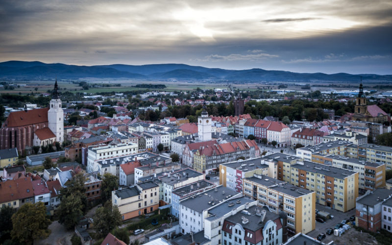 Zdjęcie panoramiczne centrum Dzierżoniowa. Ujęcie z lotu ptaka. Na pierwszym planie miejska zabudowa. w tle góry i niebo.