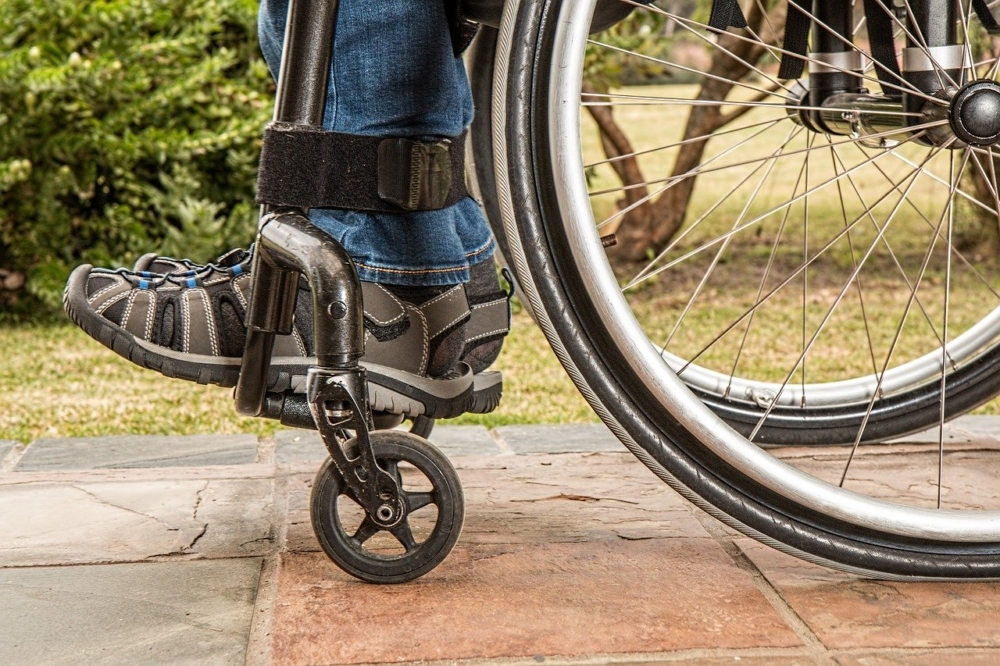 Fragment wózka inwalidzkiego. Na platformie wózka zdjęcie stóp człowieka siedzącego na wózku.