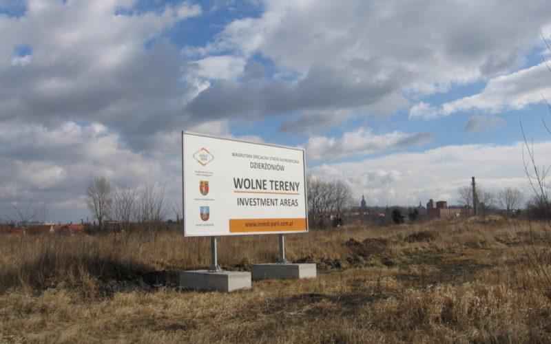 Na zdjęciu teren inwestycyjny niezabudowany. Na pierwszym planie widać tablicę reklamową promującą teren pod sprzedaż.