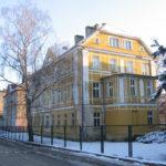 Zdjęcie przedstawia budynek po zamkniętym Zespole Szkół w Pieszycach od strony ul. Mickiewicza. Budynek ma fasadę w kolorze żółtym.