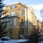 Zdjęcie przedstawia budynek po zamkniętym Zespole Szkół w Pieszycach od strony Urzędu Miasta i Gminy Pieszyce. Budynek ma fasadę w kolorze żółtym.