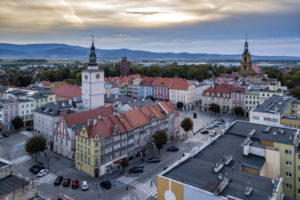 Widok na rynek Dzierżoniowa z lotu ptaka. Na pierwszym planie urząd miejski z wieżą ratuszową. W tle zabudowa miejska i niebo.
