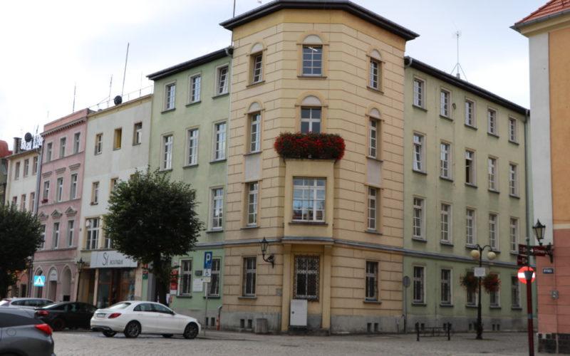 Na zdjęciu budynek starostwa powiatowego w rynku w Dzierżoniowie. Widać budynek w kolorze żółto-zielonym. Przed budynkiem zaparkowane samochody.