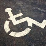 Zdjęcie fragmentu ulicy z namalowanym farbą symbolem osoby siedzącej na wózku inwalidzkim