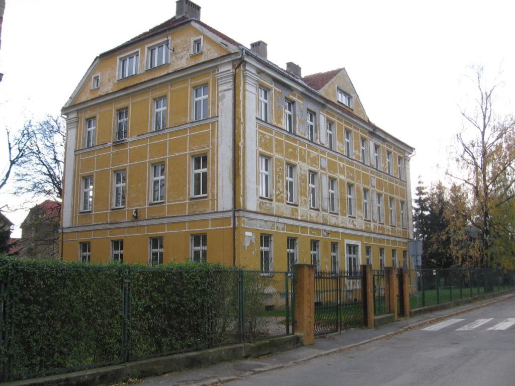 Budynek po szkole w Pieszycach. Obiekt w kolorze żółtym z wieloma oknami, otoczony płotem. Przed budynkiem ulica i przejście dla pieszych.
