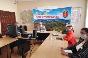 Na zdjęciu sala obrad starostwa. Za stołem ułożonym w literę U widać pięć siedzących osób. Zdjęcie ukazuje również projektor wyświetlający obraz na ekranie, a w tle ściankę z napisem Powiat Dzierżoniowski.
