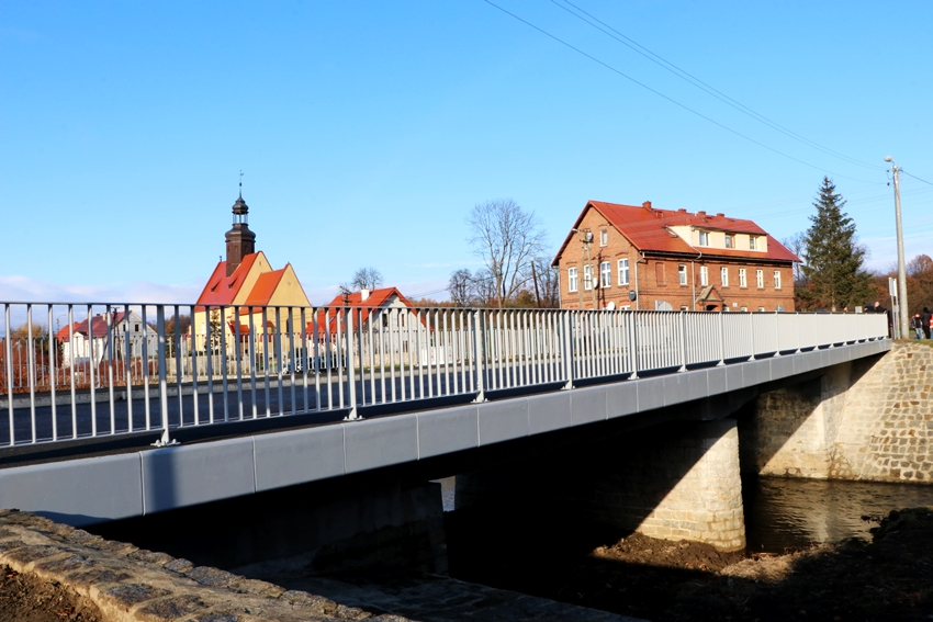 Na pierwszym planie most stalowy widziany z boku. Poniżej płynie rzeka. Po drugiej stronie mostu budynki mieszkalne i wieża kościoła.
