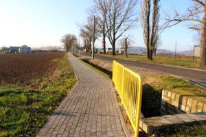 Na głównym planie chodnik z żółtą barierką ochronną. Po prawej stronie droga, a po lewej pole uprawne.