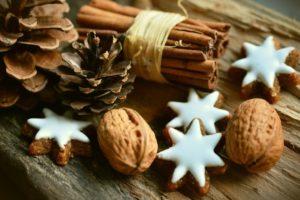 Na stole leżą ozdoby świąteczne, oraz ciastka świąteczne, orzechy włoskie i szyszka