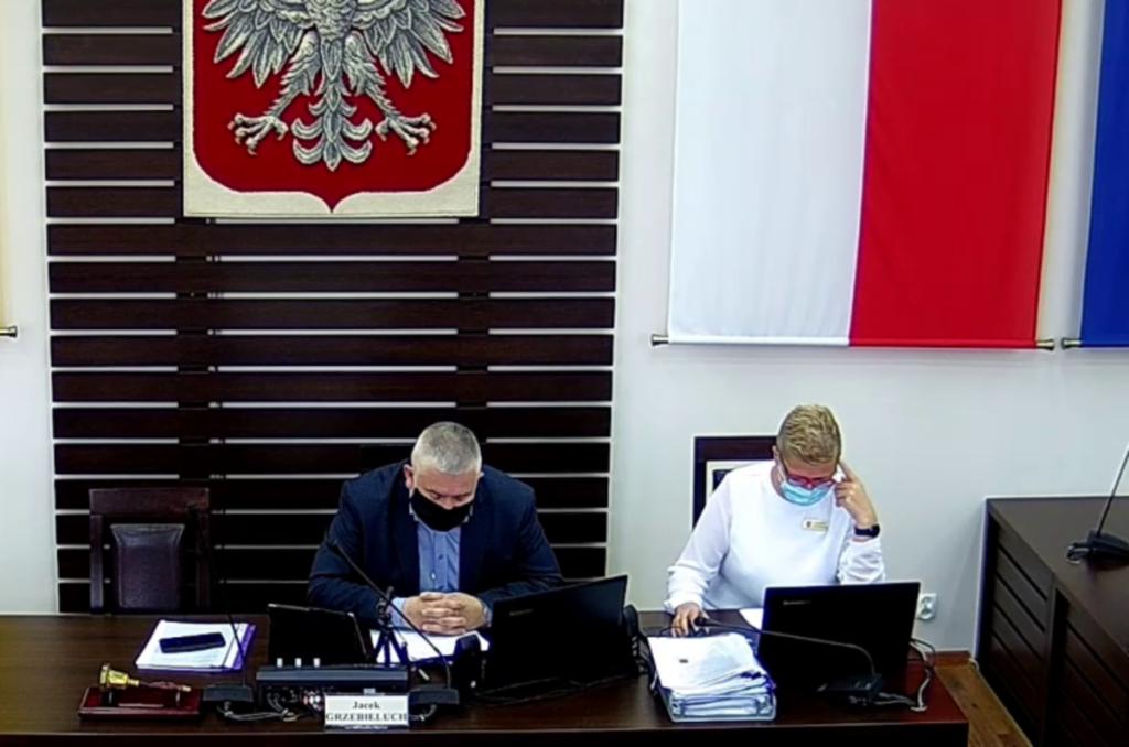 Zdjęcie sali sesyjnej Rady Powiatu Dzierżoniowskiego. Na zbliżeniu widać dwie osoby siedzące za stołem prezydialnym. Widzimy przewodniczącego Rady Powiatu oraz pracownika Starostwa. W tle widać flagę i godło RP.