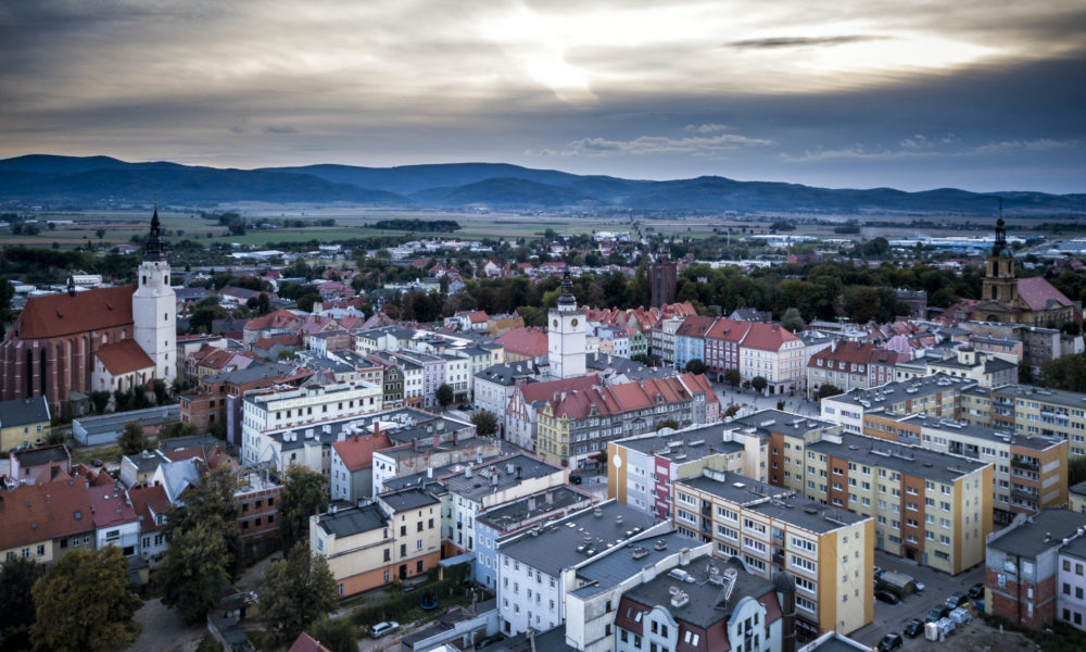 widok z lotu ptaka na rynek w Dzierżoniowie. Zabudowa rynku na pierwszym planie. W oddali góry i lekko zachmurzone niebo.
