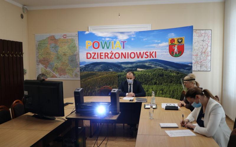 Na zdjęciu sala obrad starostwa. Za stołem ułożonym w literę U widać cztery siedzące osoby. Zdjęcie ukazuje również projektor wyświetlający obraz na ekranie, a w tle ściankę z napisem Powiat Dzierżoniowski.