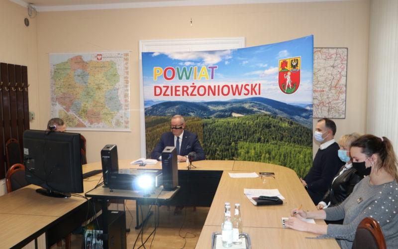Na zdjęciu sala obrad starostwa. Za stołem ułożonym w literę U widać 5 siedzących osób. Zdjęcie ukazuje również projektor wyświetlający obraz na ekranie, a w tle ściankę z napisem Powiat Dzierżoniowski.