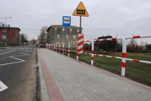 Na zdjęciu nowy chodnik z kostki betonowej wraz z barierkami ochronnymi i znakami drogowymi. W tle widać budynek wielorodzinny