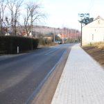 Chodnik po prawej stronie zdjęcia. Po lewej droga. W tle zabudowania mieszkalne