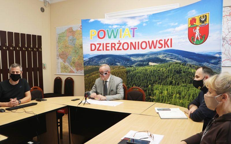 Na zdjęciu sala obrad starostwa. Za stołem ułożonym w literę U widać 4 siedzące osoby Zdjęcie ukazuje również projektor wyświetlający obraz na ekranie, a w tle ściankę z napisem Powiat Dzierżoniowski.