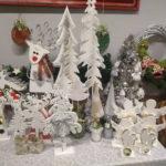 Zdjęcie przedstawia ozdoby świąteczne stojące w grupie na stoliku. Widać ręcznie wykonane z drewna ozdoby w kolorze białym, przedstawiające choinki, renifery, aniołki.