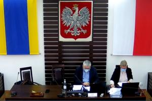 Zdjęcie sali sesyjnej Rady Powiatu Dzierżoniowskiego. Na zbliżeniu widać dwie osoby siedzące za stołem prezydialnym. Widzimy przewodniczącego Rady Powiatu oraz kierownika Biura Rady Powiatu. W tle widać flagę i godło RP.