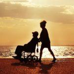 Zdjęcie plaży w czasie zachodzącego słońca. Brzegiem spaceruje osoba, która pcha wóżek z osobą niepełnosprawną. W tle morze