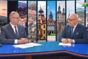 Na zdjęciu widać siedzących za stołem telewizyjnym Starostę Grzegorza Kosowskiego oraz dziennikarza. W tle grafika atrakcji turystycznych regionu.