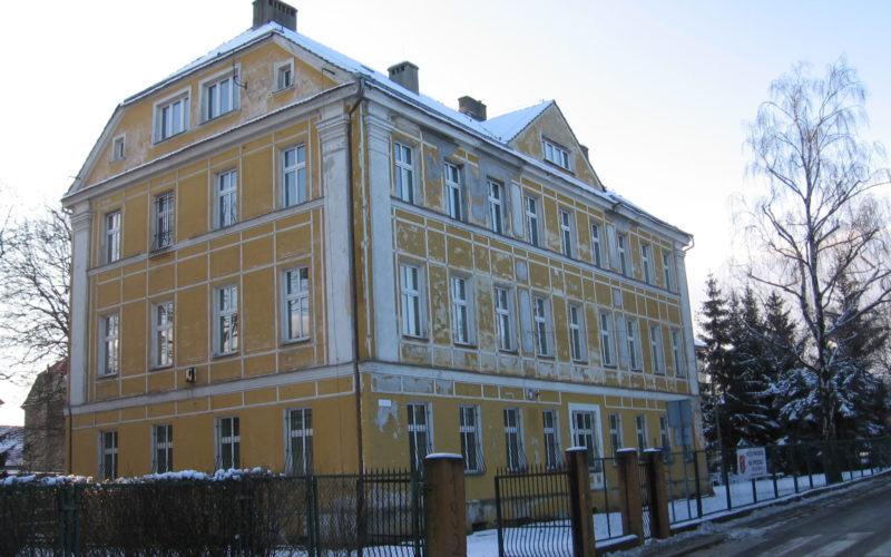 Budynek internatu w Pieszycach. Budynek w kolorze żółtym z ogrodzeniem