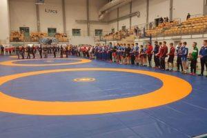 Zdjęcie zawodów zapaśniczych., Na pierwszym planie maty zapaśnicze. Wokół nich stoją zawodnicy podczas uroczystości otwarcia zmagań sportowych.