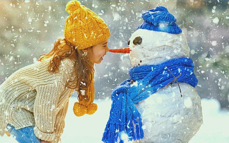 """Plakat konkursu """"Zimowe Góry Sowie"""" organizowanego przez Stowarzyszenie Turystyczne Gmin Gór Sowich oraz Nadleśnictwo Świdnica. Zdjęcie w tle pokazuje dziewczynkę dotykającą swoim nosem marchewkowego nosa bałwana. Dziewczynka ma na sobie jasny sweter i niebieskie spodnie oraz żółta czapkę i szalik. Bałwan ma na sobie niebieską czapkę i szalik. Dookoła pada śnieg."""