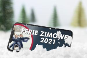 Banner informujący o Feriach Zimowych 2021 roku. Grafika przedstawiająca telefon komórkowy wrzucony w śnieg, na którego ekranie wyświetlana jest informacja o feriach, a w lewym rogu ekranu zdjęcie ilustrujące zabawę dziecka z opiekunką na sankach. W tle rozmazane świerki.
