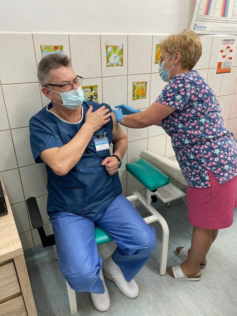 Na zdjęciu moment szczepienia lekarza przeciwko covid-19. Lekarz siedzi, a zstrzyk wykonuje pielęgniarka.