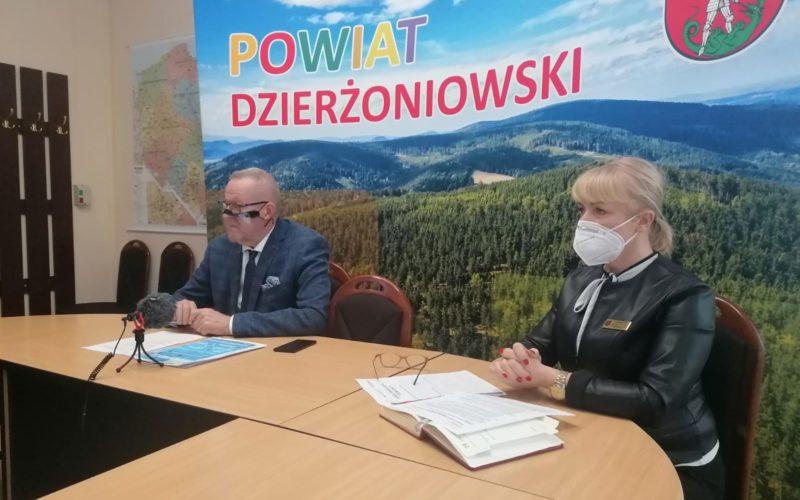 Zdjęcie sali konferencyjnej. Na pierwszym planie siedzą za stołem dwie osoby. W tle ścianka promocyjna z napisem Powiat Dzierżoniowski