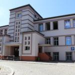 Na zdjęciu budynek szkoły w ujęciu panoramicznym. Widać budynek trzykondygnacyjny z wejściem głównym. Cały obiekt w kolorze beżowym.