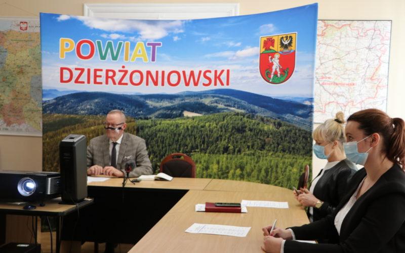 Na zdjęciu sala obrad starostwa. Za stołem ułożonym w literę U widać trzy osoby siedzące osoby. Zdjęcie ukazuje również projektor wyświetlający obraz na ekranie, a w tle ściankę z napisem Powiat Dzierżoniowski.