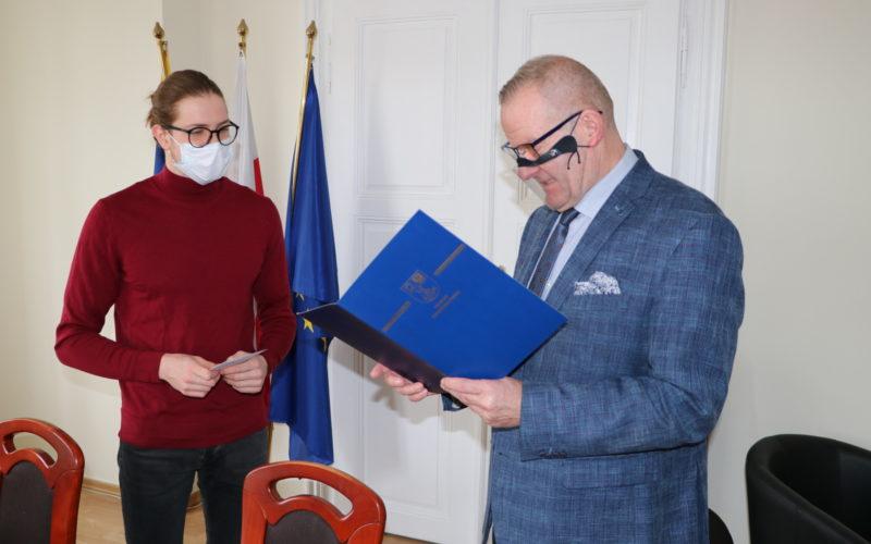 Starosta czyta gratulacje dla Pawła Juraszka w gabinecie w starostwie