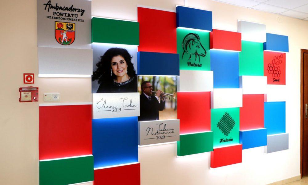 Zdjęcie ścianki promującej ambasadorów powiatu. Ściana składająca się z bloków kolorowych z fotografiami wyróżnionych osób.