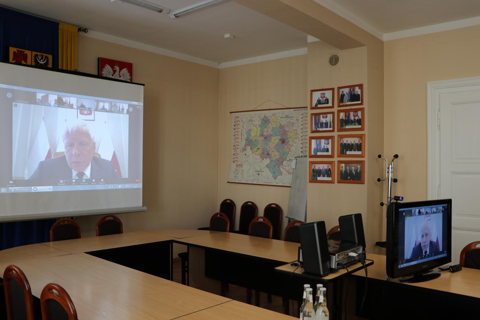 Na zdjęciu sala obrad starostwa. Na stole ułożonym w literę U w prawej części zdjęcia telewizor wyświetlający rozmówcę. Po lewej stronie ten sam obraz wyświetlony na ekranie z rzutnika stojącego obok telewizora. nad ekranem godło, herb i flaga powiatu.