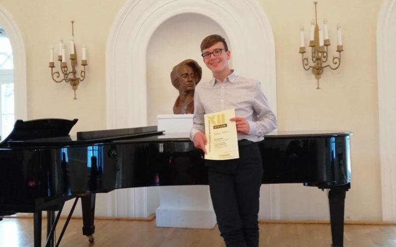 Na zdjęciu osoba trzymająca w dłoni dyplom, oparta o czarny fortepian. W tle popiersie Fryderyka Chopina koloru brązowego na białym postumencie. Na ścianach kinkiety z pięcioma żarówkami każdy.
