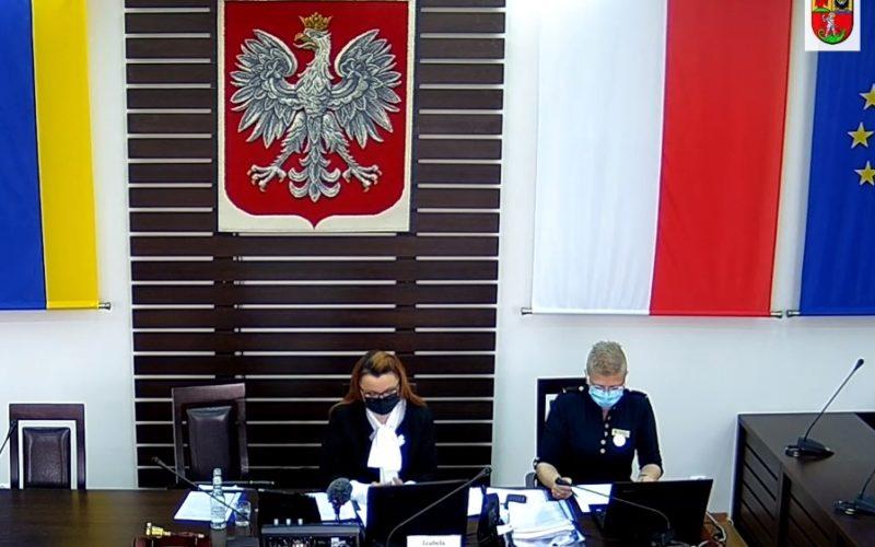 widok na prezydium rady. Za stołem siedzą dwie osoby, za nimi godło.