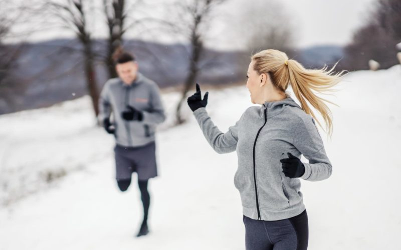 Na zdjęciu widać biegnąca parę - kobietę oraz mężczyznę, w zimowej scenerii. Kobieta wyciągniętym palcem zaprasza mężczyznę do dalszego biegu.