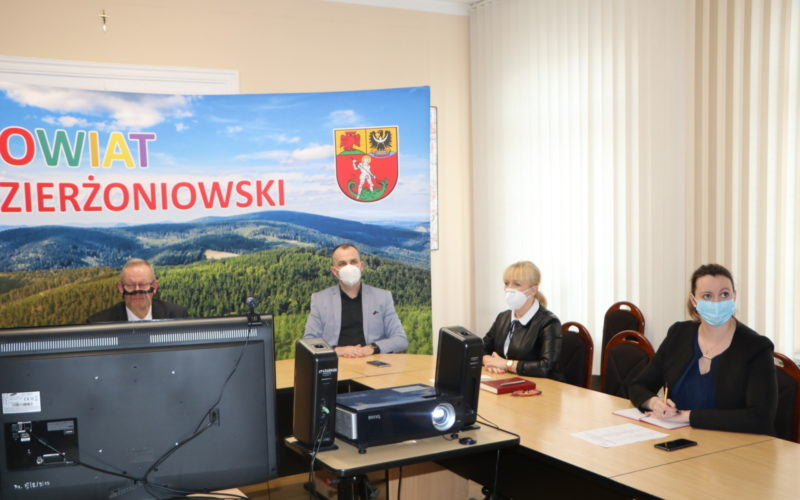 Na zdjęciu siedzą za stołem w sali konferencyjnej 4 osoby. Za nimi ścianka promocyjna Powiatu