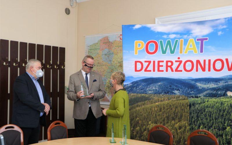 Sala konferencyjna. Przewodniczący Rady Powiatu i Starosta Dzierżoniowski wręczają podziękowania przedstawicielowi sztabu WOŚP