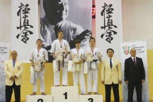na podium stoją zawodnicy z nagrodami i w kimonach. Obok sędziowie