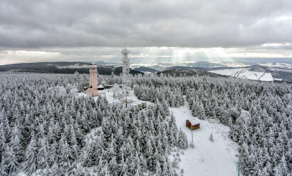 widok z lotu ptaka na zimowy krajobraz gór sowich. w tle wieża widokowa na wielkiej sowie