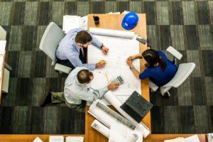 Zdjęcie od góry stołu za którym siedzą po obu stronach 3 osoby nad dokumentami.