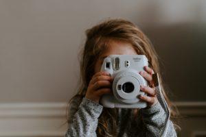 portret dziewczynki trzymającej aparat przy twarzy