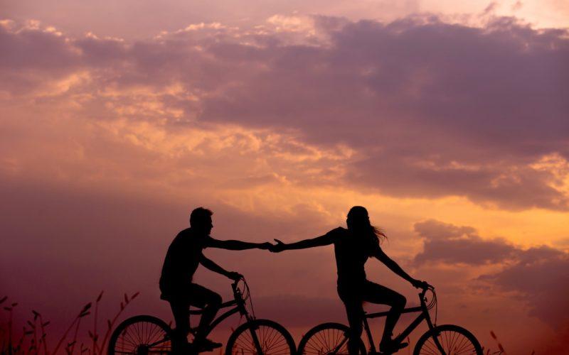 Para jadąca na rowerach i trzymająca się za ręce. W tle zachód słońca