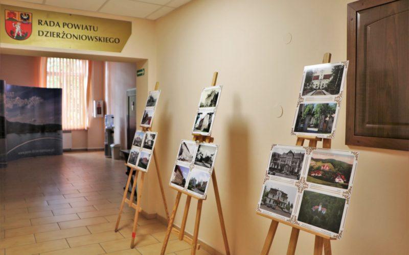 Na zdjęciu widnieje wystawa zdjęć na sztalugach pod nazwą Powiat Dzierżoniowski wczoraj i dziś. Wystawa znajduje się w korytarzu Starostwa Powiatowego w Dzierżoniowie przy ulicy Świdnickiej 38 na pierwszym piętrze.